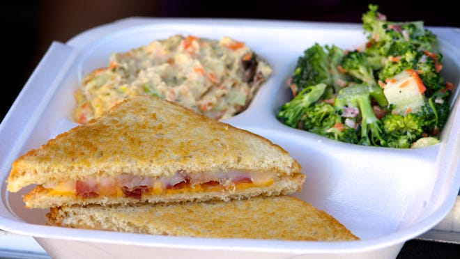 The Jersey Girl Super Foods food truck features a variety of grilled cheese sandwiches, including this one, the Fort Monmouth, with bacon, tomato, provolone and cheddar. Also in the box: potato salad and broccoli salad.