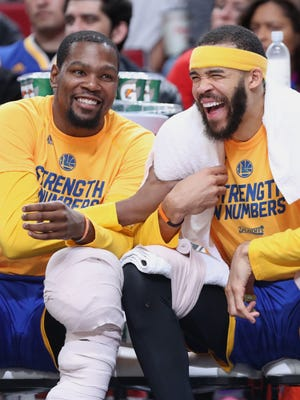 Golden State Warriors forward Kevin Durant, center JaVale McGee and guard Stephen Curry react in the closing the seconds of a 128-103 win over the Portland Trail Blazers to clinch Game 4 of the first round of the 2017 NBA Playoffs.