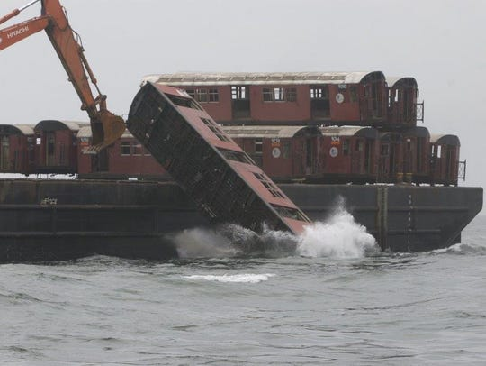 Old New York City subway cars are knocked off a barge