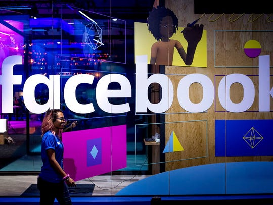 In this April 18 file photo, a conference worker passes a demo booth at Facebook's annual F8 developer conference, in San Jose, California.