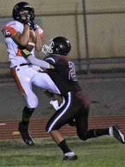 Capitan's Tanner Lowrance catches a pass under heavy pressure Friday night.