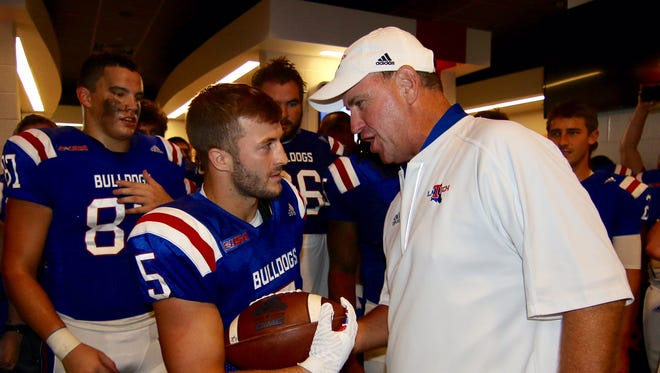 Louisiana Tech coach Skip Holtz, right, gives the game ball to wide receiver Trent Taylor. The senior broke the school record for receptions in Saturday's win over Rice.