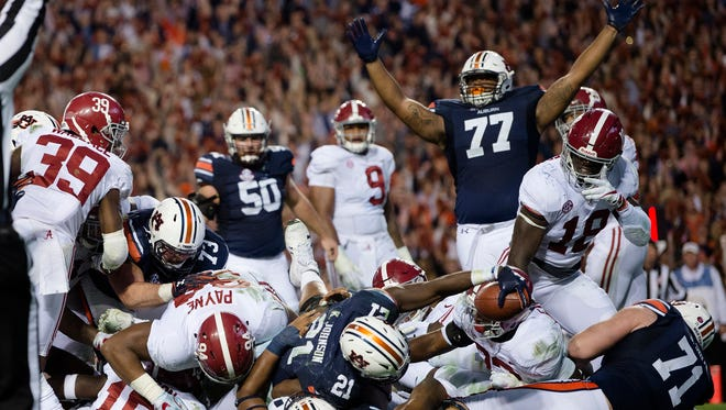 Auburn running back Kerryon Johnson (21) reaches over the goal line for the go ahead touchdown during the Iron Bowl NCAA football game between Auburn and Alabama on Saturday, Nov. 25, 2017, in Auburn, Ala.