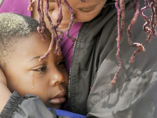 A tearful ZiAire Sweatman-Clark, 7,  is embraced by his family after being returned to his York city home. ZiAre had been reported missing and was found safely after spending the night at someone's home without his parents' knowledge.