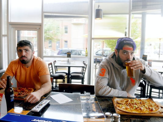 From left, Nate Jacobs of West Manchester Township and Ben Sallade of West York eat pizza and drink beer together as they watch a sports channel on Wednesday, June 3, 2015, at BrewVino in York. The restaurant, which opened in October 2014, features specialty pizzas and a rotating roster of craft beer and wines.