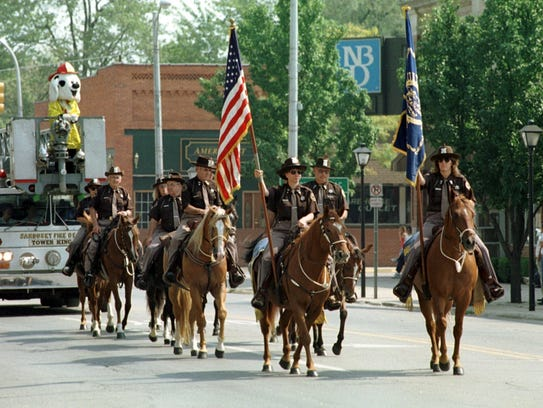 The Sanilac County Sheriff's Posse leads a parade in
