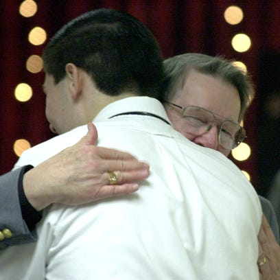 Ralph Burkhardt gives former student Christopher Flory a hug as they are recognized during the Richmond High School Academic Excellence Awards banquet in 2001.