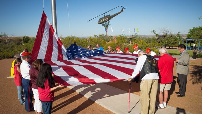 Visitors to Veterans Memorial Park, including City of Las Cruces mayor Ken Miyagishima, right, raise the United States flag, May 20, 2016.