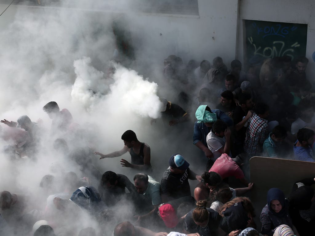 Policemen try to disperse hundreds of migrants by spraying them with fire extinguishers during a gathering for a registration procedure at the stadium on the Greek island of Kos.