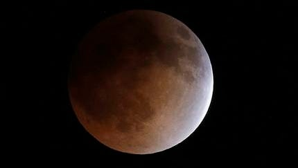 In this Tuesday, April 15,  file photo, the moon turns an orange hue during a total lunar eclipse in the sky above Phoenix. On Wednesday morning, North Americans will have prime viewing of a full lunar eclipse, especially in the West. The total eclipse will last an hour, until sunrise on the East Coast.