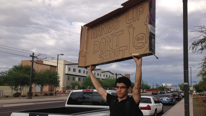 """Robert Ramirez, 21, drove to his first protest on his first day of classes at ASU. He waved a homemade sign that said """"hands up, don't shoot"""" while overlooking Jefferson Street."""
