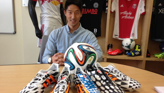 In this May 28, 2014 photo, Peter Hong, merchandise manager for adidas, poses with the company's Battle Pack collection of soccer boots and the Brazuca, the official ball of the 2014 World Cup, at the conpany's headquarters in Portland, Ore. (AP Photo/Anne Peterson)