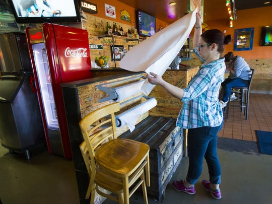 Server Amy Horn tears paper to cover a table at the