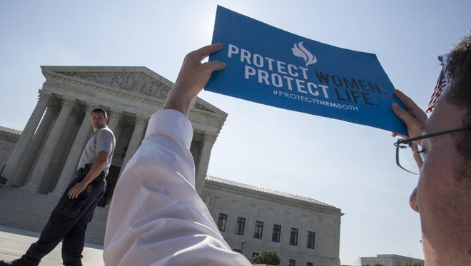 An anti-abortion activist stands in front of the Supreme Court.