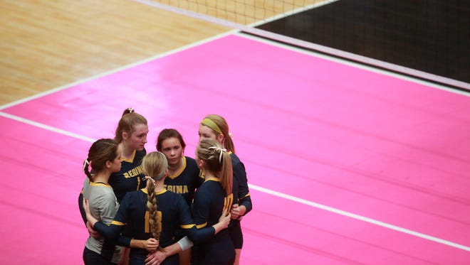 Regina teammates huddle up during the Regals' Class 2A first round state tournament game against Western Christian at the U.S. Cellular Center in Cedar Rapids on Wednesday, Nov. 8, 2017.