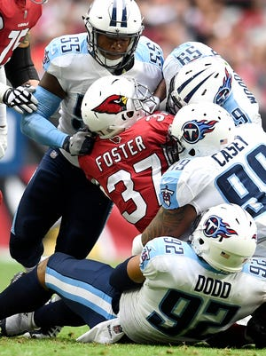 The Titans defense swarms Cardinals running back D.J. Foster (37) during the first half at University of Phoenix Stadium Sunday, Dec. 10, 2017 in Glendale, Ariz.