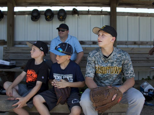 Dylan Reinert, right, of the Cashtown Pirates waits next to his little brother Nolan, middle, and Curtis Rebert, left, during a doubleheader in the South Penn League.