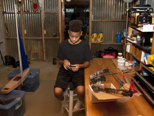 "Latrell Alston, 13, is learning how to use a hunting bow from his ""Big Brother"" Jay Brenneman. He and his brother have been Brenneman's ""little brothers"" since 2014."