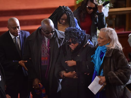 Sarah Butler's parents, Victor and Lavern Butler, middle, being escorted from the church. Butler, 20, of Montclair, a student at at New Jersey City University, was slain while home for Thanksgiving break.
