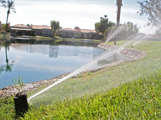 Sprinklers run in July 2013, keeping the lawns green in a neighborhood in Rancho Mirage.