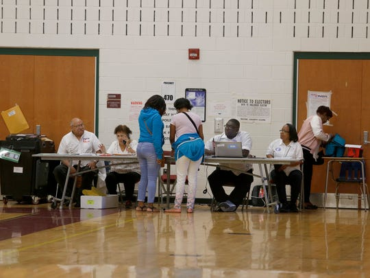 Voting poll workers help voters for the primary election at Western International High School on Tuesday, August 8, 2017 in Detroit.