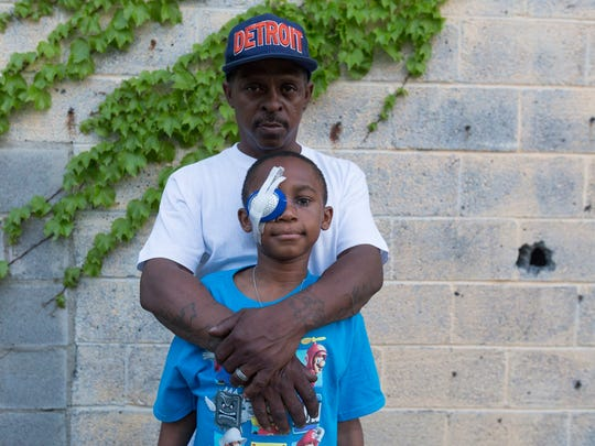 Cecil Cosey holds his son Malik Cosey, 9, both of Detroit, on Wednesday, May 17, 2017, in Detroit.