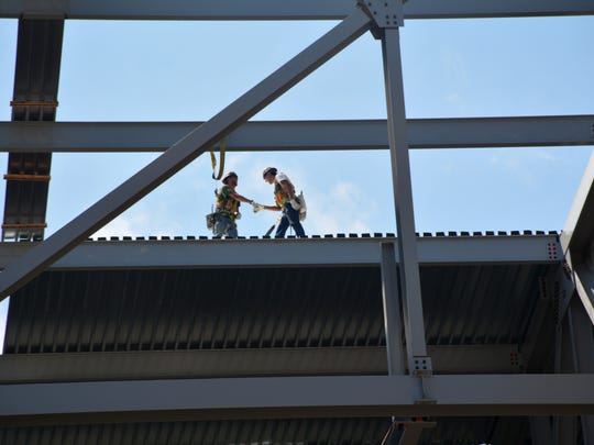 Workers install some of the last remaining roof panels recently at the Milwaukee Bucks arena. The topping off ceremony for the project is Thursday.