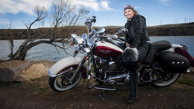 """Shelley Oswood straddles her 2013 Harley Davidson Heritage Classic bike by the Missouri River Friday, April 14. Her favorite scenic drive is the Beartooth Highway that winds through Montana and Wyoming. """"The twistier and turnier the better,"""" Oswood said."""