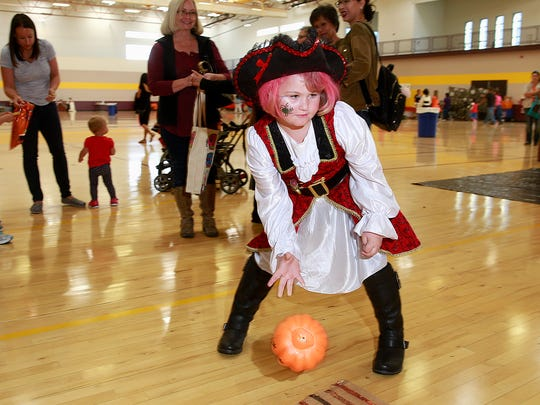 Emma Marriott, 6, goes pumpkin bowling during the San Juan College Halloween Carnival on Saturday at the college.