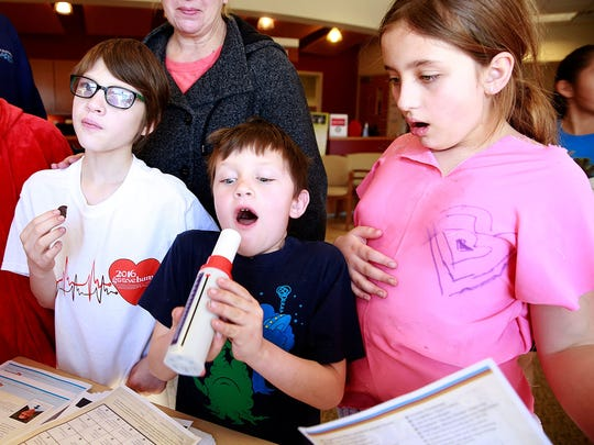 Paiten Hubbs, 9, left; Tripp Hubbs, 6; and Tristi Dorenkamp, 10, take turns blowing into a peak flow meter to measure lung capacity during the A Fair of the Heart and Goosebump Race on Feb. 13, 2016, near the San Juan Regional Medical Center. The event returns this weekend.