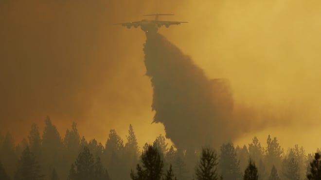 A tanker flies through smoky air as it drops retardant on a wildfire near Omak, Wash.