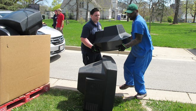 Jeremiah Vianes (left) and Robert Mitchell, who both work in logistics at the Milwaukee VA Medical Center, carry a television dropped off Tuesday during a free electronics recycling event held in honor of Earth Day. The electronics will be recycled by federal prisoners learning vocational skills.