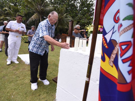 Liberator Gene Bell places a lit candle on the base of a monument cross during a memorial service, to honor the World War II victims of the Fena Cave massacre, at the Old Agat Cemetery on Wednesday, July 19, 2017.