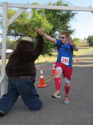 A runner connects with Smokey Bear for a flying high five at the 2015 Smokey Bear Fun Run in Capitan.