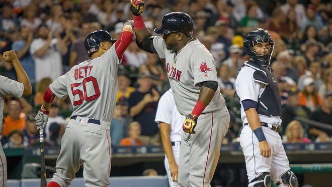Red Sox DH David Ortiz hits a two-run home run in the top of the fifth inning and high-fives teammate Mookie Betts during the Tigers' 3-2 loss Saturday at Comerica Park.