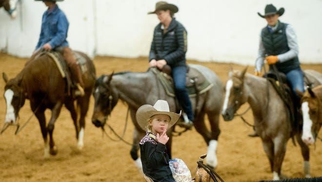 Clara Ashlock, 6, eats a snack on horseback as others warm up for competing in the Abilene Winter Circuit Cutting Thursday at the Taylor County Expo Center. Ashlock competed in the junior youth event.