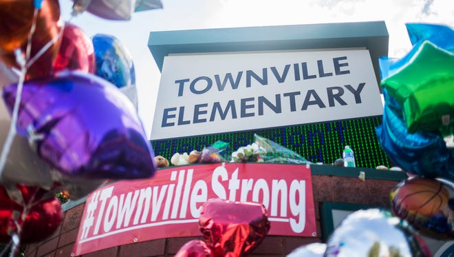 A memorial with supportive notes, stuffed animals, flowers, and balloons is set up outside Townville Elementary on Oct. 1 in Townville.