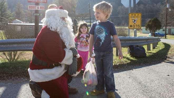 Jordan Howard, dressed as Santa Claus, talked with Kedan Matthews, 5, after handing him Christmas gifts. In the background is 3-year-old Lexy Brown. Howard filled in as Santa for his father, Mike, who has been the Mountain Santa for years in Harlan County.
