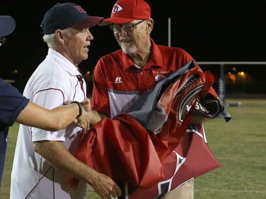 La Quinta coach Dan Armstrong gives the flag to Palm Desert coach Pat Blackburn, Friday, September 25, 2015.
