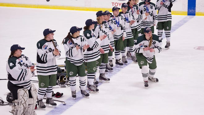The Vermont Shamrocks line up to collect their winners' medals after a 2-1 win against the Connecticut Northern Lights in the USA Hockey Tier II girls hockey national championship at Cairns Arena on Monday.