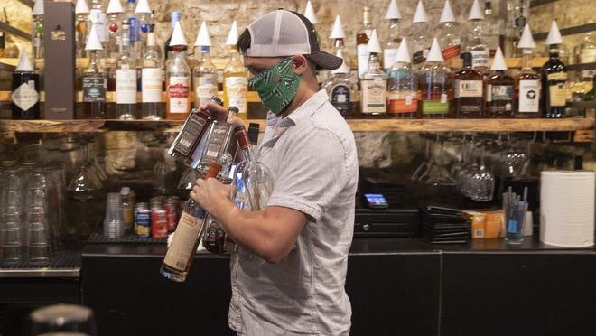John Hardie, assistant manager of Cedar Street Courtyard, removes some bottles before closing the bar on West Fourth Street in June, after Gov. Greg Abbott ordered all bars in Texas to be closed due to the coronavirus. Some Texas bars could reopen the Texas Alcoholic Beverage Commission voted this week to ease restrictions.