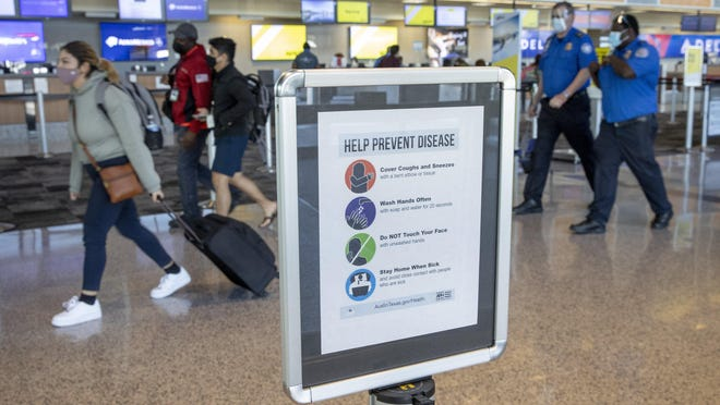 Travelers and TSA workers wear masks in the ticketing area at Austin-Bergstrom International Airport last Wednesday. Doctors recommend wearing a mask at all times on a plane and using hand sanitizer and sanitizing wipes to clean your seating area.