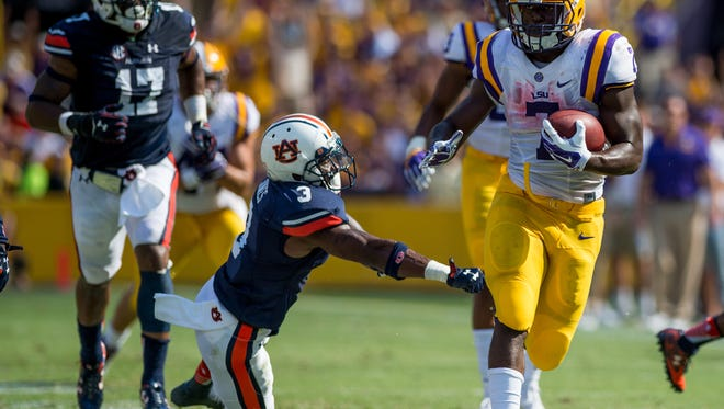 LSU Tigers running back Leonard Fournette (7) runs through a tackle attempt by Auburn Tigers defensive back Jonathan Jones (3) before scoring a 40-yard touchdown during the first half of NCAA football game at Tiger Stadium in Baton Rouge, La., Saturday, Sept. 19, 2015.