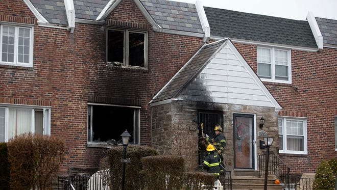Firefighters enter a burned out home in the aftermath of a fatal fire Tuesday, Dec. 9, 2014, in Philadelphia. A firefighter was trapped in the basement of the burning row home early Tuesday, becoming the first female member of the Philadelphia Fire Department to die in the line of duty, officials said.