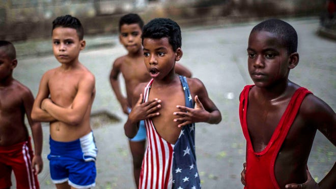 In this Oct. 15, 2014, file photo, 8-year-old Yodimiler Arias, along with fellow wrestlers, listen to instruction from their teacher, in a park in Old Havana, Cuba.