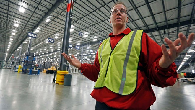 In this Dec. 12, 2014 photograph, Brian Miller, Nissan's senior supply chain manager, explains the process where workers sort, stack and ready for shipping a flow of auto parts, at the company's 1.5-million-square-foot integrated logistics center in Canton, Miss. Nissan is focusing on improving its parts supply as it works to increase production capacity at its Mississippi plant. (AP Photo/Rogelio V. Solis)