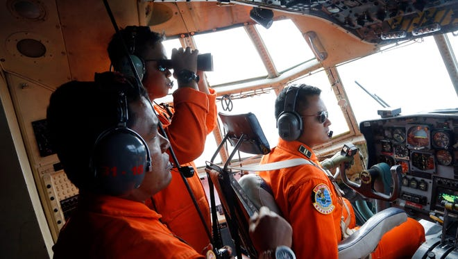 Crew of Indonesian Air Force C-130 airplane of the 31st Air Squadron scan the horizon during a search operation for the missing AirAsia flight 8501 jetliner over the waters of Karimata Strait in Indonesia, Monday, Dec. 29, 2014. Search planes and ships from several countries on Monday were scouring Indonesian waters over which the AirAsia jet disappeared, more than a day into the region's latest aviation mystery. Flight 8501 vanished Sunday in airspace thick with storm clouds on its way from Surabaya, Indonesia, to Singapore.