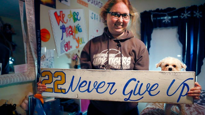 Mount St. Joseph University basketball player Lauren Hill holds a sign made for her, which she keeps in her room, along with many other messages and gifts of support. Her dog, Sophie, is at her side.