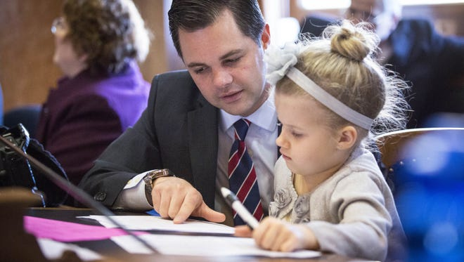 Rep. Zach Nunn, left, organizes his desk with his daughter, Addi, 7, before the opening session of the House of Representatives at the 2015 Session of the 86th Iowa General Assembly in Des Moines, Iowa, Monday Jan. 12, 2015.