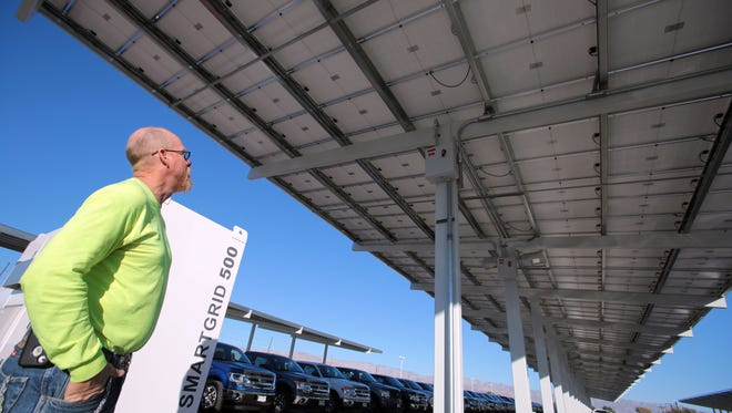 Jon Sherwood, a foreman with La Salle, stands under the solar array his company recently installed for Fiesta Ford in Indio. Photo taken on Tuesday, January 13, 2015.